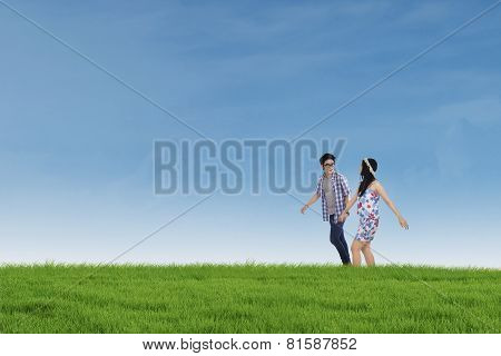 Romantic Couple Walking Together On The Meadow