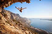 image of fail-safe  - Female rock climber falling of a cliff while lead climbing - JPG