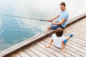 stock photo of cheers  - Top view of cheerful father and son fishing together while sitting at the riverbank - JPG