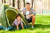 stock photo of tent  - Cheerful father and son sitting near the tent while camping in the forest - JPG