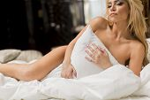 image of laying-in-bed  - Pretty young woman laying on the bed - JPG