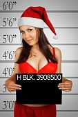 stock photo of hottie  - Pretty arrested girl in Santa costume posing over white background - JPG