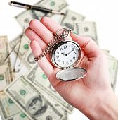 stock photo of american money  - Silver pocket clock in hand on money background - JPG