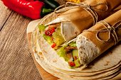 picture of mexican  - Mexican tortilla wrap with meat and vegetables on wood table - JPG