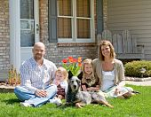 stock photo of blue heeler  - Family Sitting in Front of Their Home - JPG