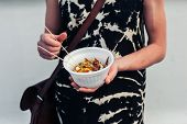 picture of squid  - A young woman is holding a paper bowl of grilled squid - JPG
