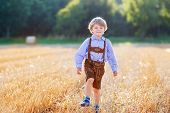 picture of hay bale  - Funny little kid boy in traditional German bavarian clothes leather shorts and check shirt walking happily through wheat field near hay stack or bale - JPG