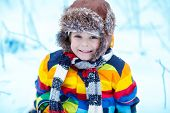 image of winter  - Winter portrait of kid boy in colorful winter clothes outdoors during snowfall - JPG