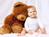 pic of baby bear  - Smiling baby playing with teddy bear on the bed home - JPG