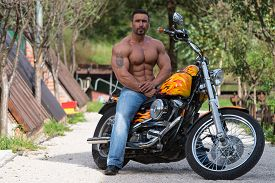 stock photo of biker  - Biker Man Bodybuilder Sits On A Bike - JPG
