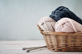 picture of coil  - Wool yarn in coils with knitting needles in wicker basket on light blue background - JPG