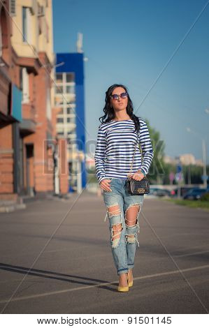 beautiful brunette girl walks through the city streets. in torn jeans and frock