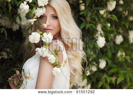 Beautiful woman in summer Park near the Bush blooming roses