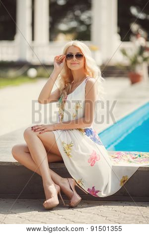 Sexy blonde sits poolside with blue water