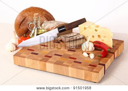 Vegetables, Cheese And Bread On A Chopping Board
