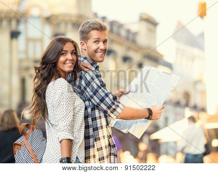 Young couple with a map in the city