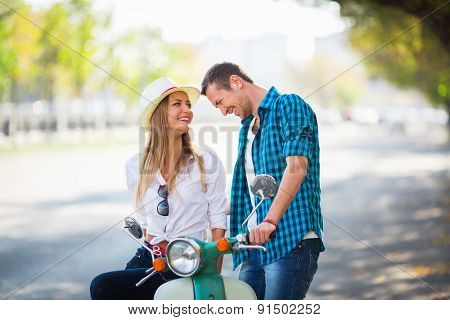Smiling couple with a scooter outdoors