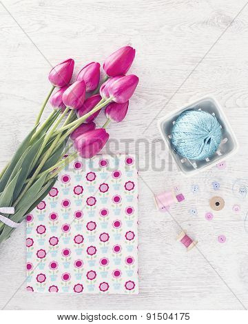 Collection Of Spools  Threads In Pink Colors Arranged On A White Wooden Background With Tulips