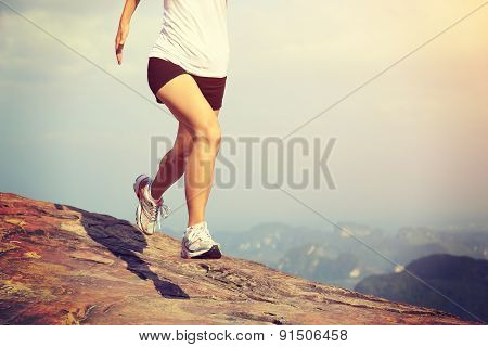 young asian woman running on mountain peak cliff