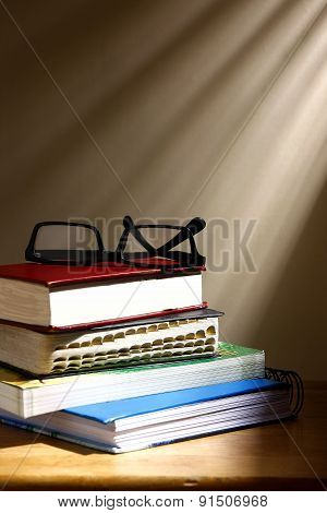 Stack of books and eyeglasses
