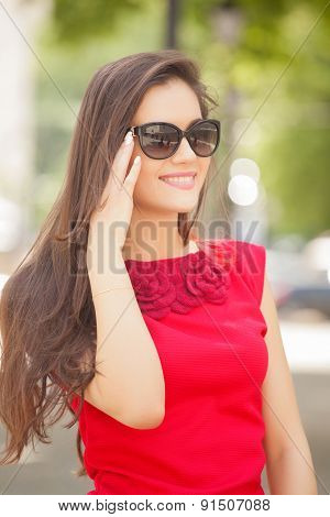 Beautiful young woman with sunglasses walking in the city. Summer photo