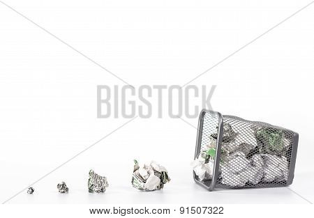 isolated fallen wastebasket full of newspaper waste paper