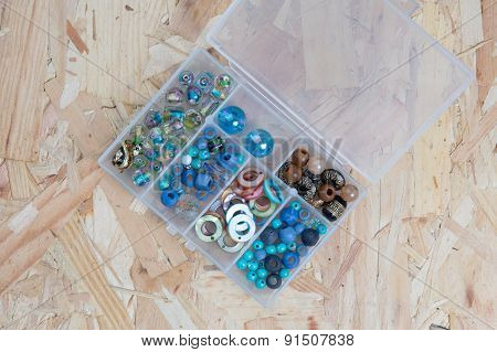 Box With Beads, Spool Of Thread, Plier And Glass Hearts To Create Hand Made Jewelry On Old Wooden Ba