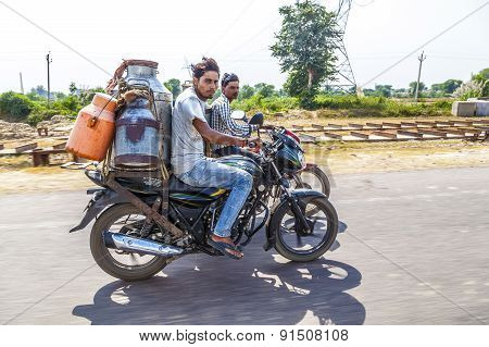 Men Riding Motorbike With Cans Of Milk