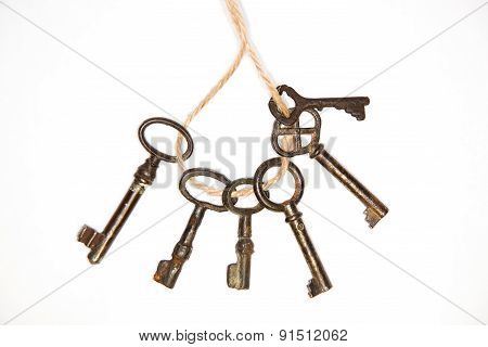 A Lot Vintage Keys On A Rope On White Background