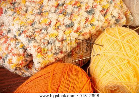 Skeins Of Yarn With Knitting Needles And Knitted Thing On Wooden Background