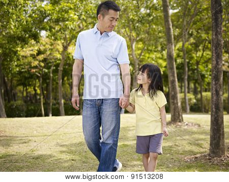 Asian Father And Daughter Takes A Walk In Park