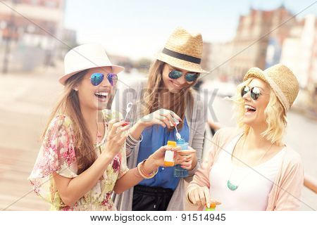 a picture of three friends blowing soap bubbles in the city