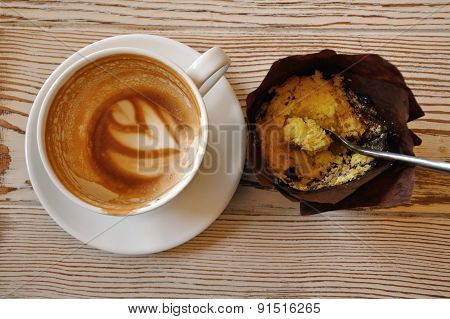 Empty coffee cup and muffin leftovers