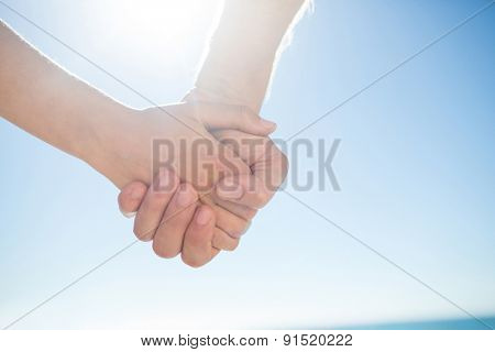 Couple walking hand in hand at the beach