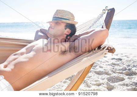 Handsome man resting in the hammock at the beach