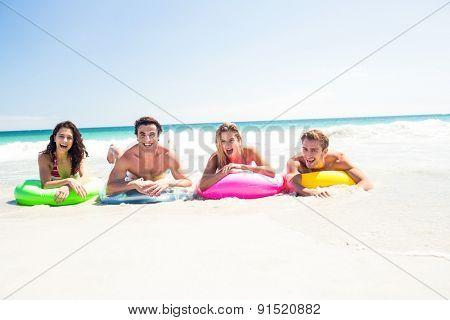 Happy friends lying on inflatable mattress above the water at the beach