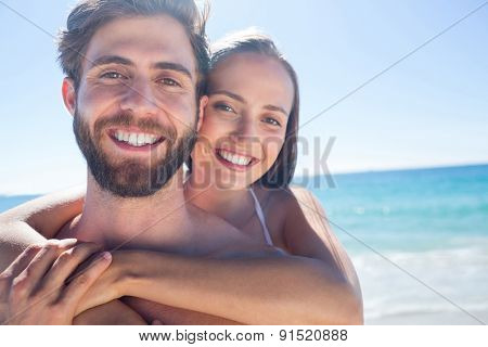 Happy couple hugging and looking away at the beach