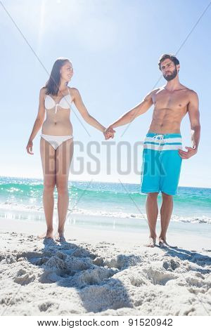 Happy couple holding hands at the beach
