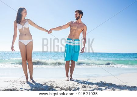 Happy couple looking at each other while holding hands at the beach