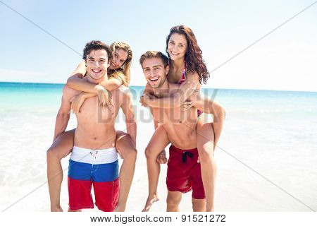 Handsome men giving piggy back to their girlfriends at the beach