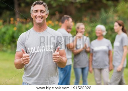 Happy volunteer with thumb up on a sunny day