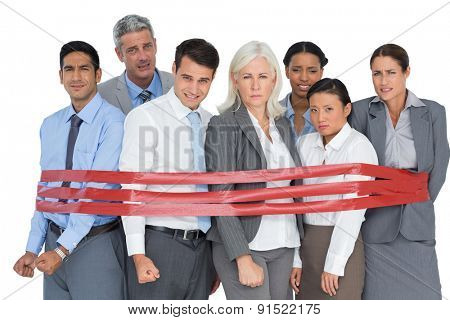 Unhappy business people surrounding by red strip in office