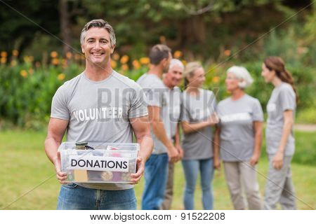 Happy man holding donations boxes on a sunny day