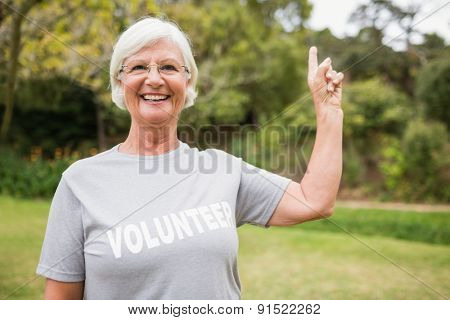 Happy volunteer grandmother with thumbs up on a sunny day