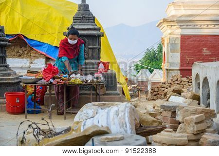 KATHMANDU, NEPAL - MAY 22, 2015: A woman sells candles, marigolds and incense among the rubble at Swayambhunath. Nepal was hit by two major earthquakes a few weeks before.