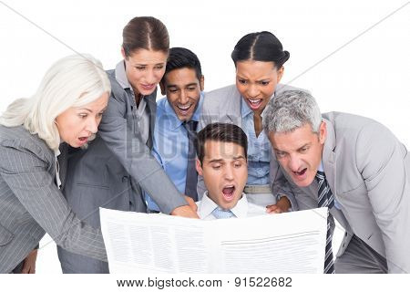 Surprising business people looking at newspaper on white background