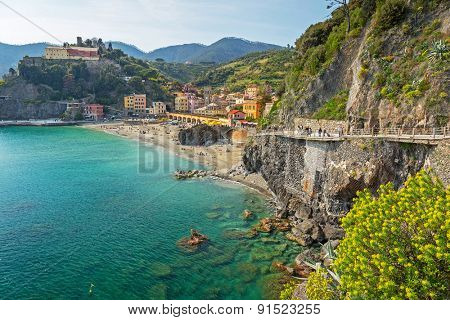 MONTEROSSO, ITALY - APRIL 12, 2015: People on the coastline of Monterosso in Italy. Monterosso is one of five famous coastline villages in the Cinque Terre National Park.