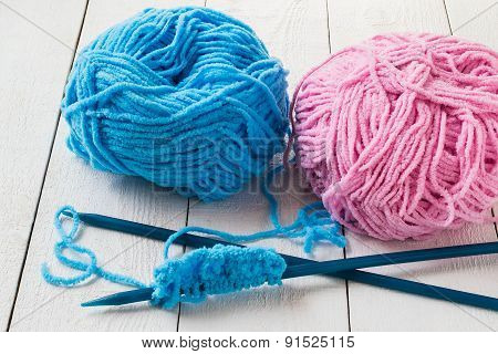 Two Skeins Of Yarn And Knitting Needles