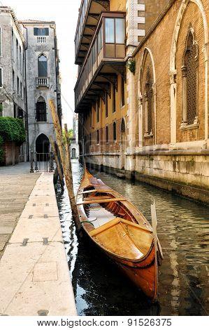 Wooden Gondola In Narrow Venetian Canal, Italy