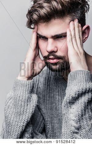 Portrait of a young man in gray pullover. Headache
